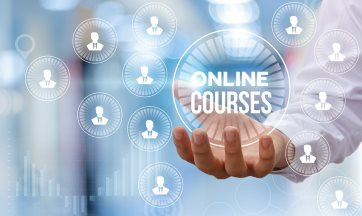 Photo of a hand holding the text Online Courses. There are various icons floating around it